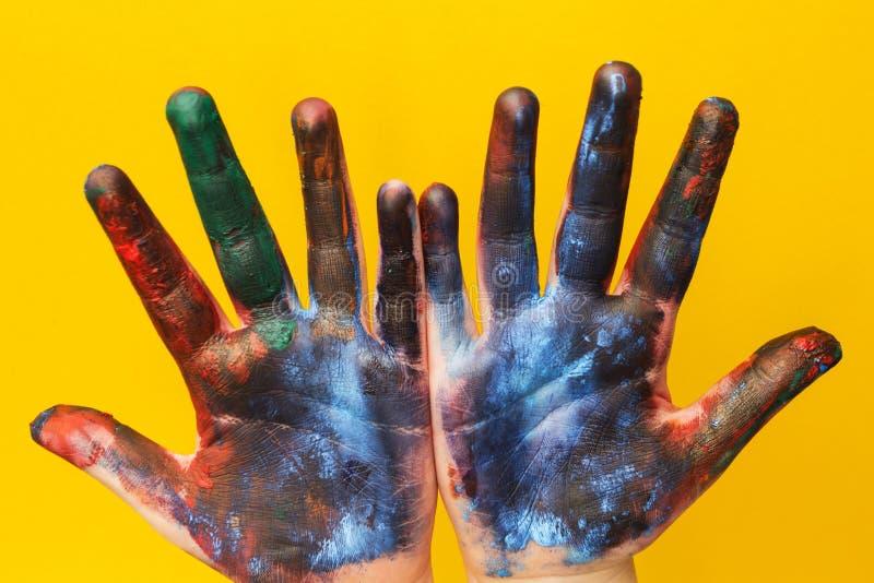 Руки детей запятнаны с пестротканой краской на желтой предпосылке стоковая фотография rf