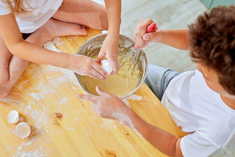 Руки детей небольшие побили тесто для блинчиков варя в кухне стоковые изображения
