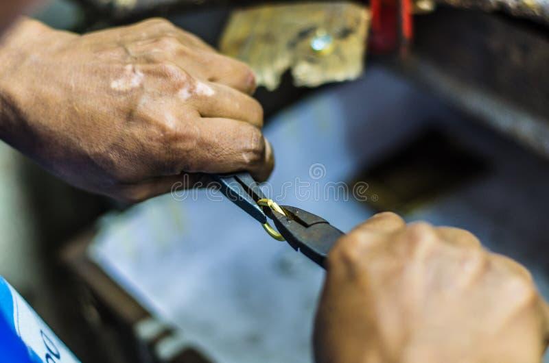 Руки деятельности ювелира на кольце с плоскогубцы стоковые фотографии rf