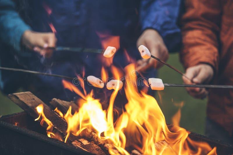 Руки друзей жаря в духовке зефиры над огнем в гриле стоковое изображение