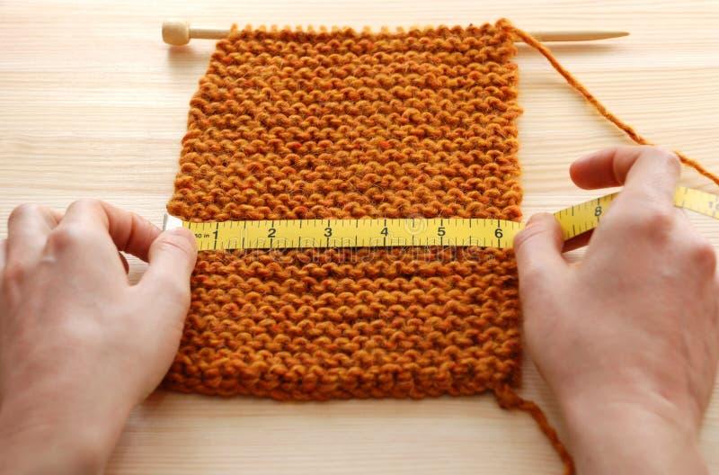 2 руки измеряя вязать в дюймах стоковая фотография rf