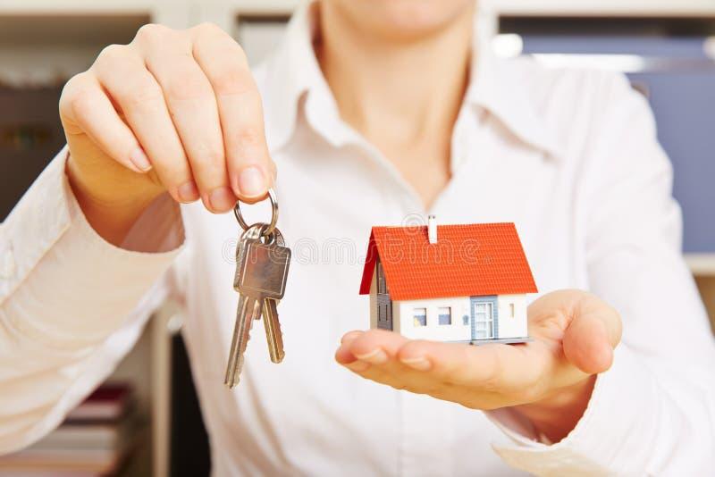 Руки держа ключи и дом стоковое изображение rf