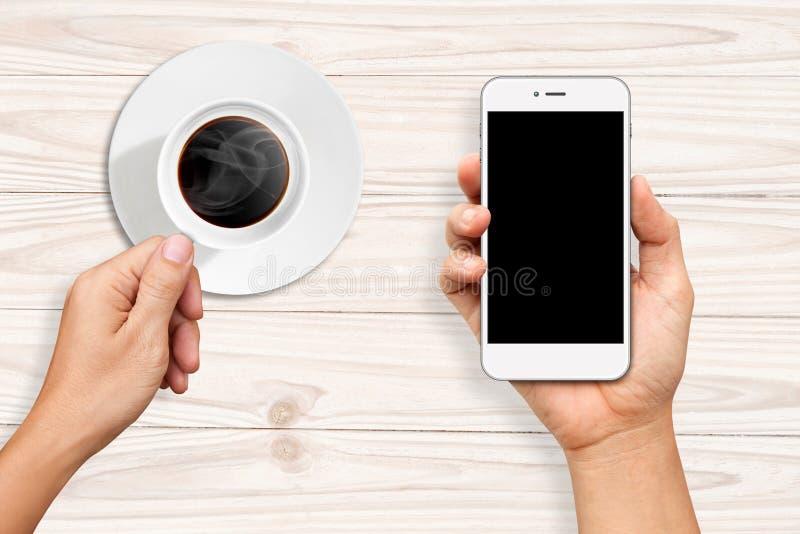 Руки держа чашку кофе и белый умный телефон стоковое фото