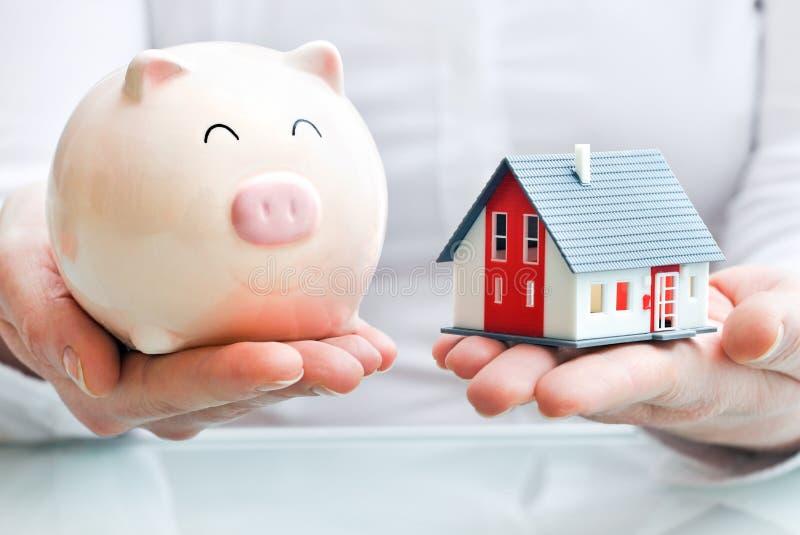 Руки держа piggy банк и дом моделируют