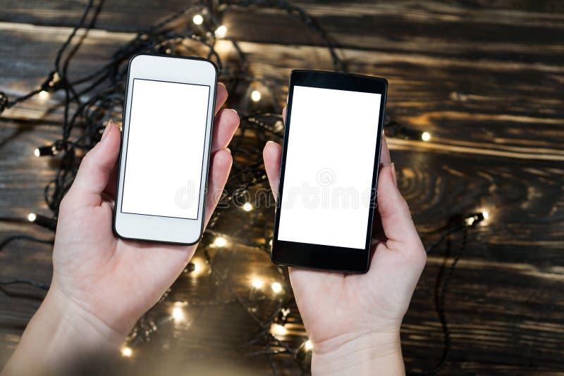 Руки держа 2 smartphones на деревянной предпосылке стоковые изображения rf