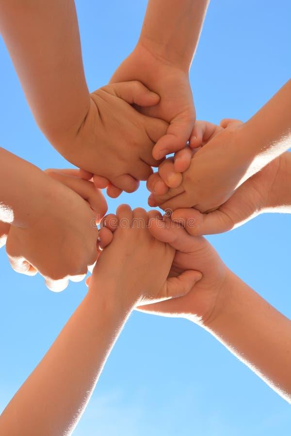 Руки детей держат один другого вокруг на предпосылке голубого неба стоковое изображение rf