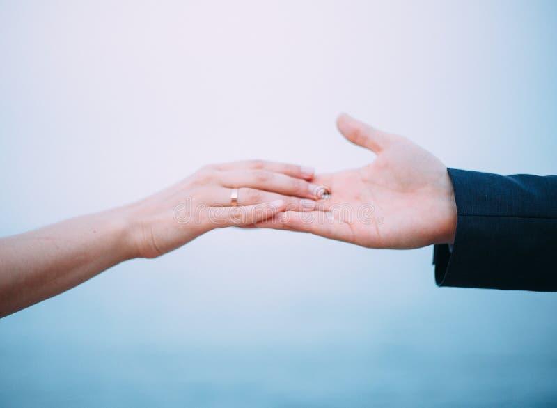 Руки жениха и невеста Обручальные кольца, свадьба моря o стоковое изображение rf