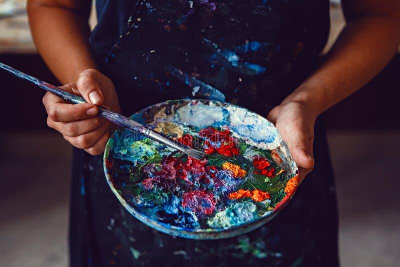 Руки женского художника держа грязную грязную палитру с различными красками и paintbrush стоковое изображение rf