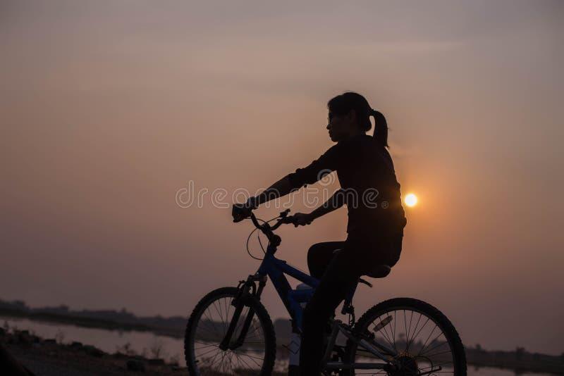 Руки женщины велосипед на заходе солнца стоковое фото rf