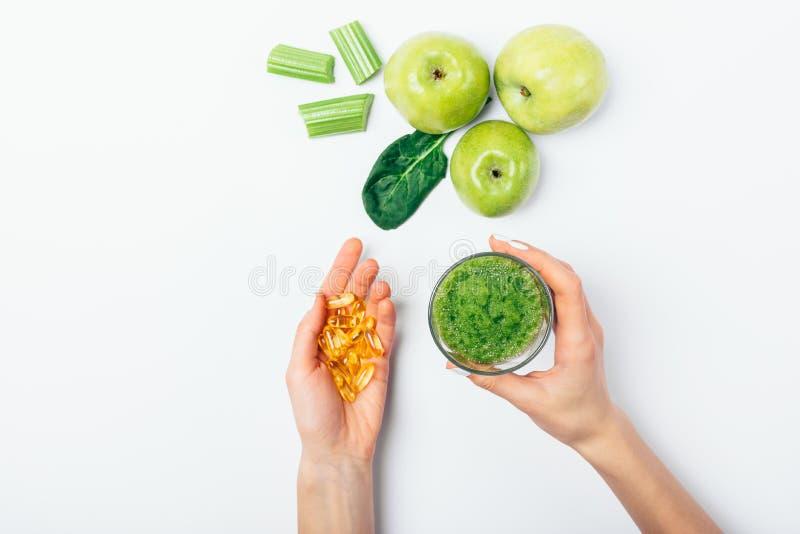 Руки женщины взгляда сверху держа стекло зеленого smoothie стоковое изображение