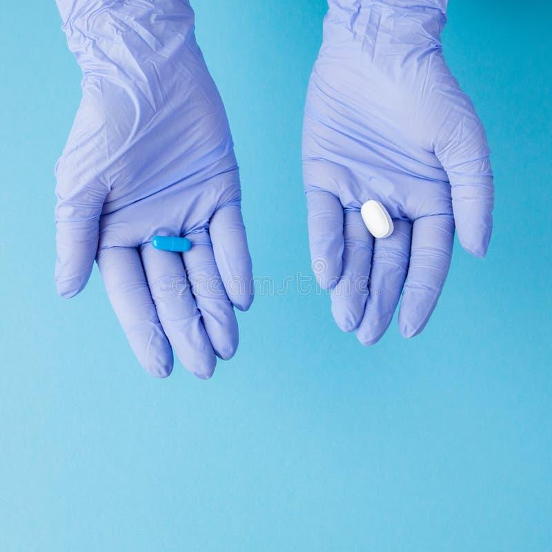Руки женщины в медицинских перчатках давая 2 больших таблетки голубая белизна Сделайте ваш выбор стоковое изображение rf