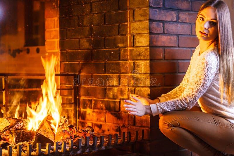Руки женщины грея вверх на камине Дом зимы стоковая фотография
