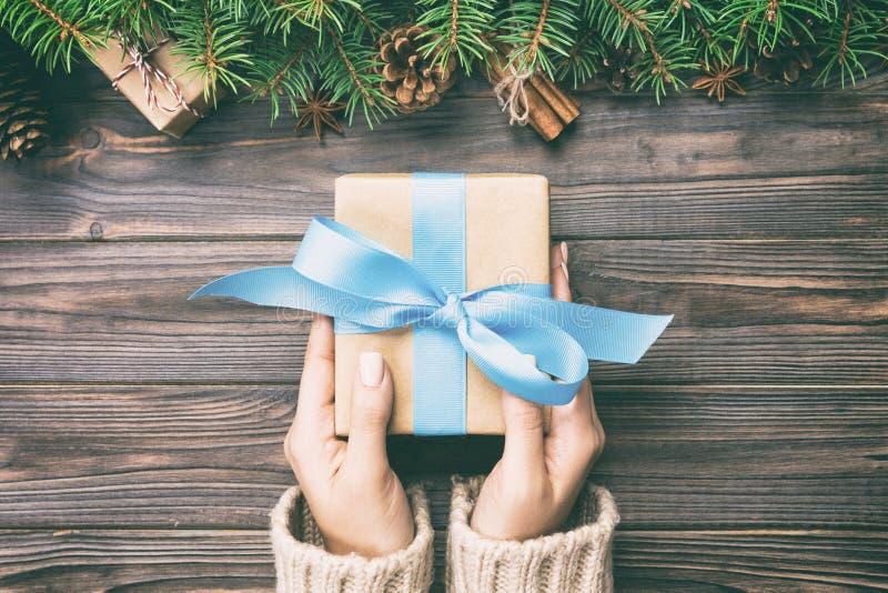 Руки женщины дают в оболочке рождеству handmade настоящий момент в бумаге с голубой лентой Присутствующая коробка на празднике на стоковое фото