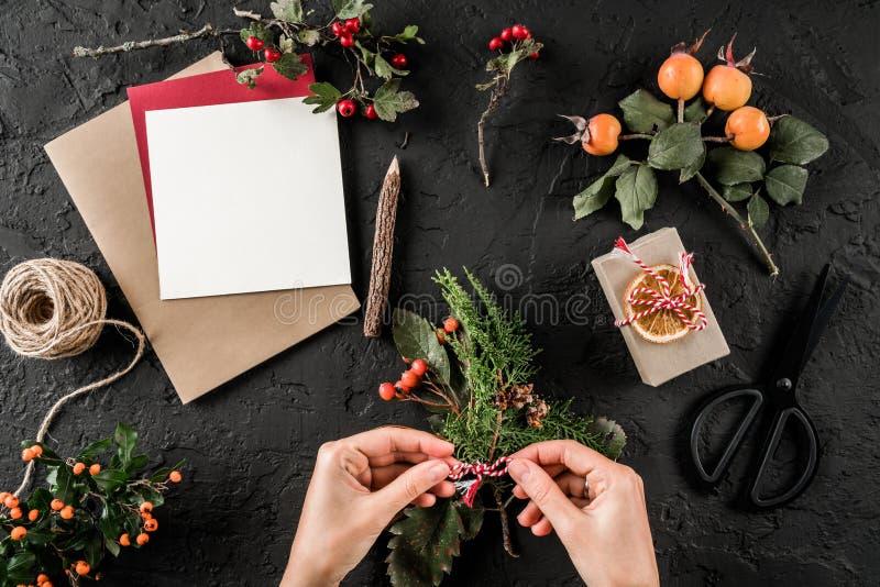 Руки женщины делая венок рождества на темной предпосылке с примечанием бумажной карты, карандашем, ножницами, ветвями ели и ягода стоковые изображения