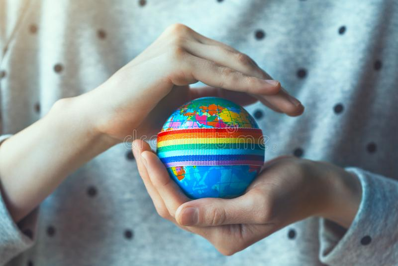 Руки женщины держа глобус с лентой радуги LGBT стоковое изображение rf