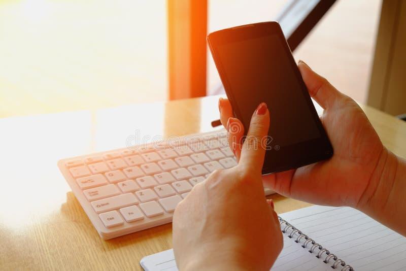 Руки женщины держа кредитную карточку и используя компьтер-книжку стоковые фото