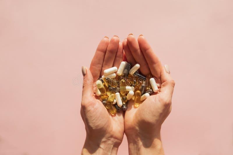 Руки женщины держа много различные таблетки или dietic дополнения стоковые изображения rf