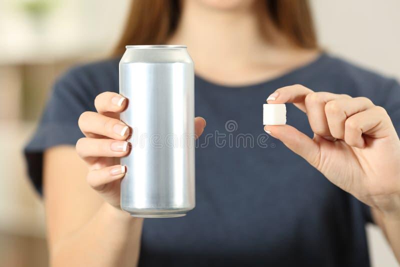 Руки женщины держа питье соды могут и куб сахара стоковое фото