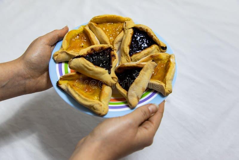 Руки женщины держа покрашенную плиту с печеньями варенья голубики и абрикоса Hamantash Purim на белой скатерти стоковые фотографии rf