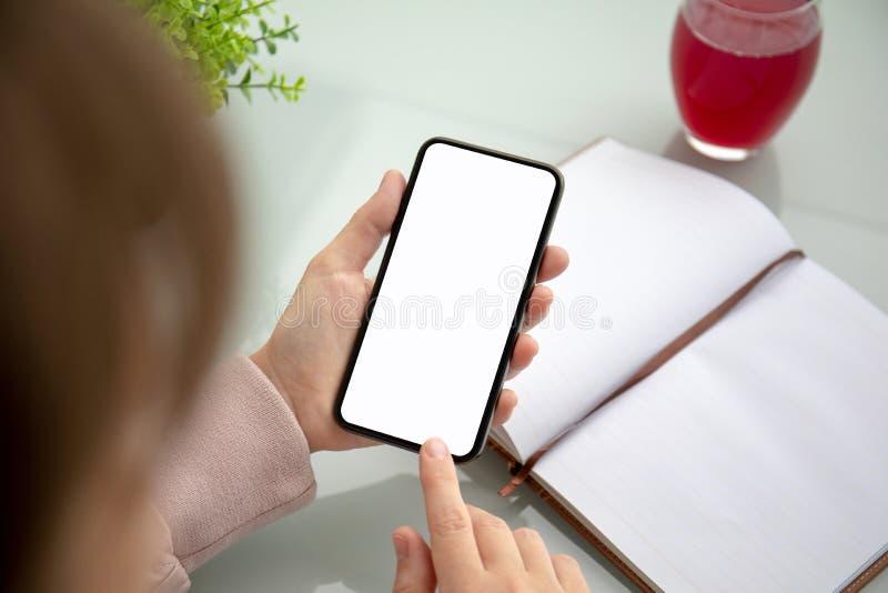 Руки женщины держа телефон касания с изолированным экраном в офисе стоковая фотография rf
