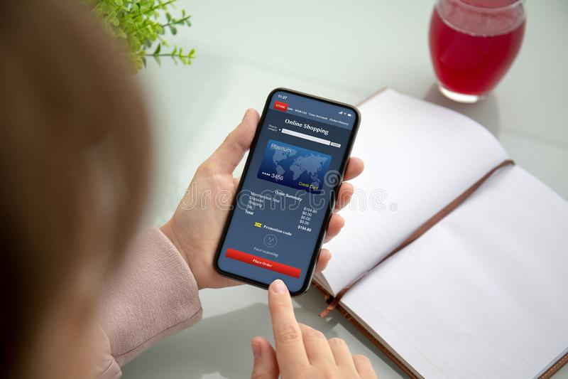 Руки женщины держа телефон с покупками приложения онлайн на экране стоковая фотография rf