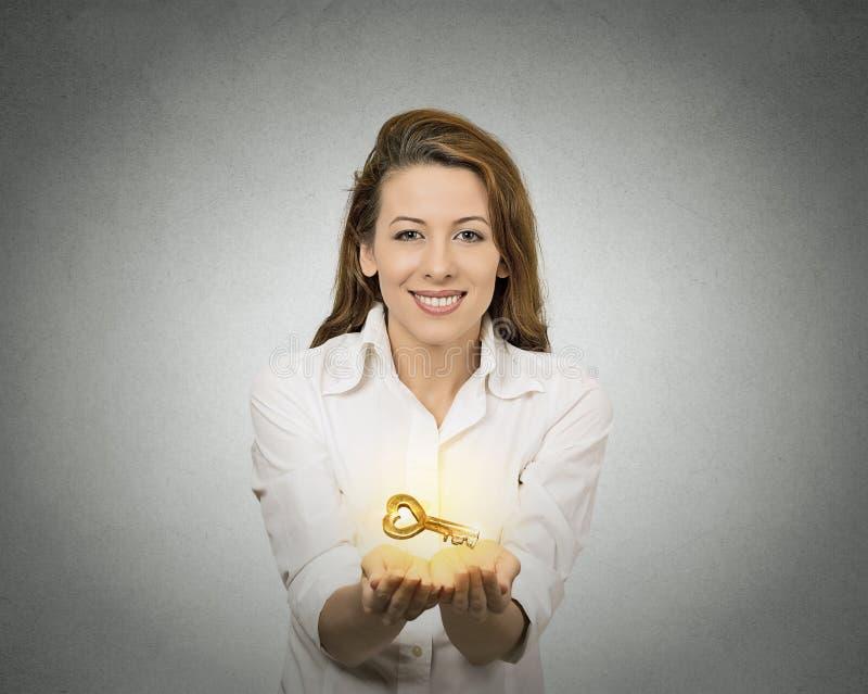 Руки женщины держа предлагая новый ключ стоковая фотография rf