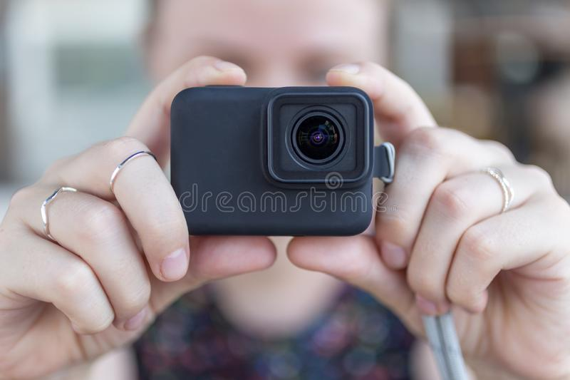 Руки женщины закрывают вверх по удержанию небольшой черной камеры действия принимая видео или фото стоковые изображения rf