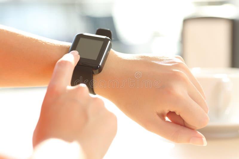 Руки женщины используя умный вахту в баре стоковое фото