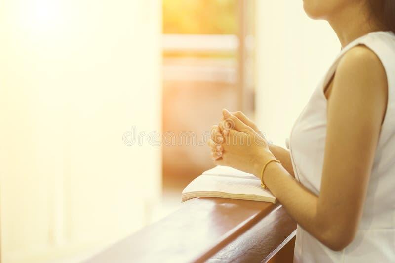Руки женщины моля на библии в церков для концепции веры, духовности и христианского вероисповедания стоковая фотография rf