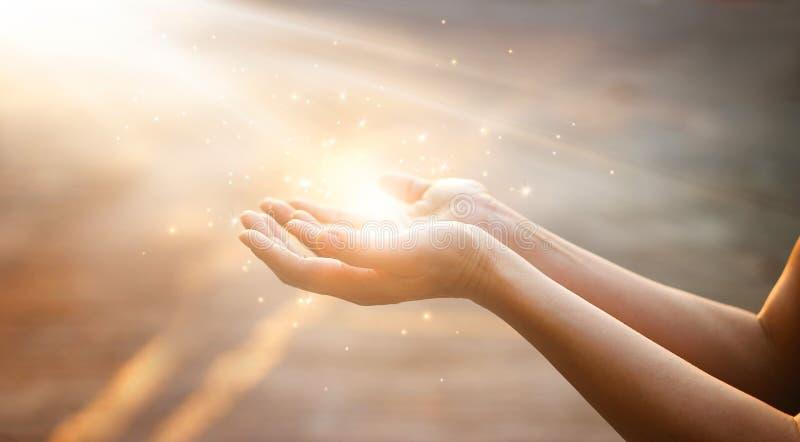 Руки женщины моля на предпосылке захода солнца стоковые изображения