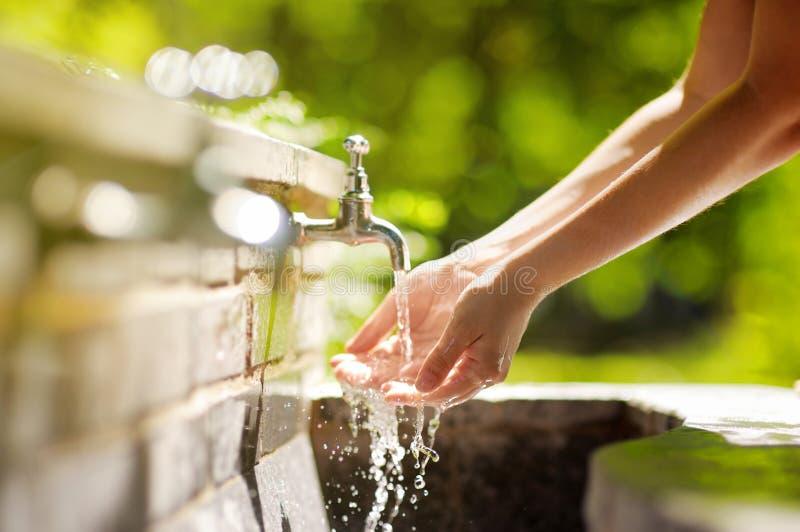 Руки женщины моя в фонтане города стоковые фотографии rf