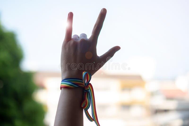 Руки женщины показывая знак любов с лентой радуги LGBTQ в утре для лесбиянки, гея, бисексуального, трансгендерный и странная общи стоковая фотография rf