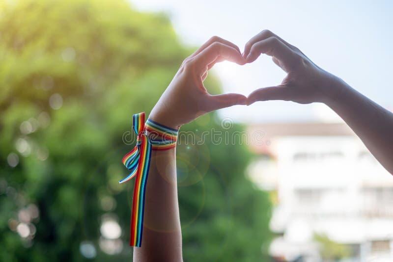 Руки женщины показывая знак формы сердца с лентой радуги LGBTQ в утре для лесбиянки, гея, бисексуального, трансгендерный и странн стоковые фотографии rf