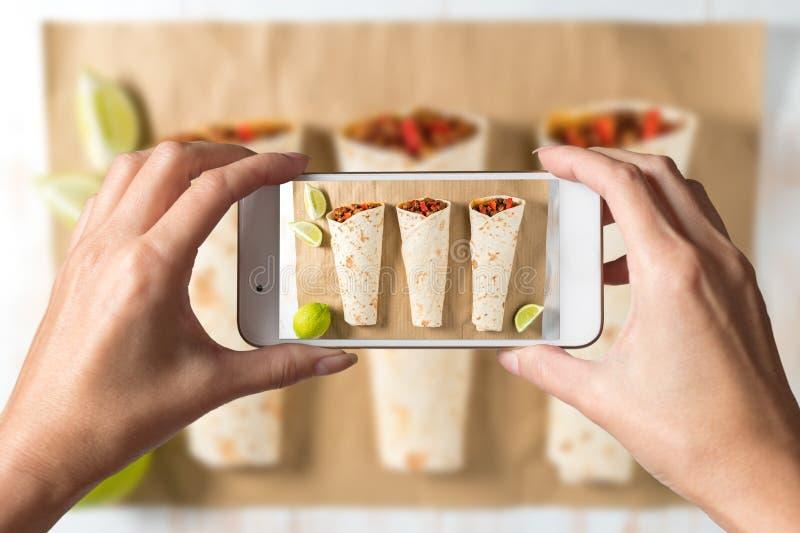 Руки женщины принимая фото вкусного домодельного буррито с овощами и говядиной на бумаге стоковые фотографии rf