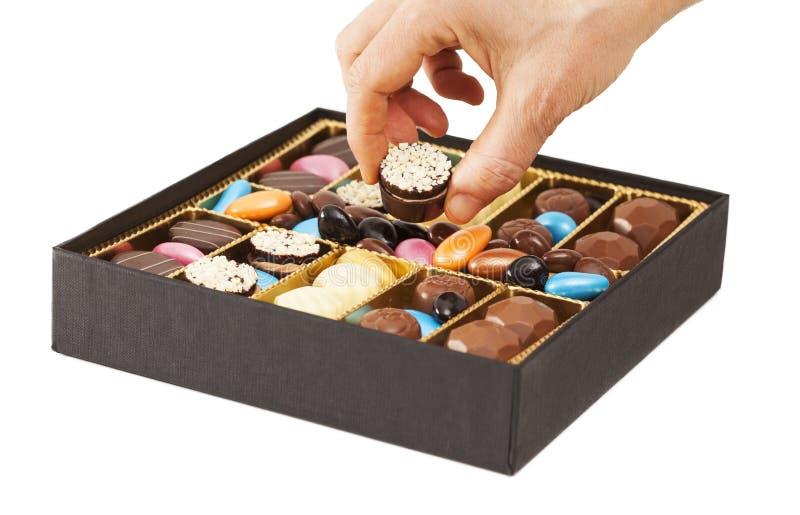 Руки женщины принимая шоколад в коробке стоковая фотография