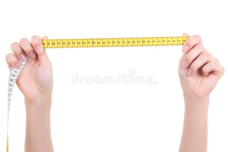 Руки женщины протягивая ленту измерения изолированную на белом backgrou стоковые фото