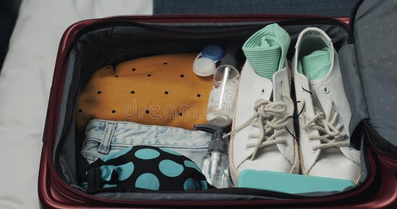 Руки женщины распаковывая чемодан для путешествия на кровати дома Подготовки перемещения стоковое фото