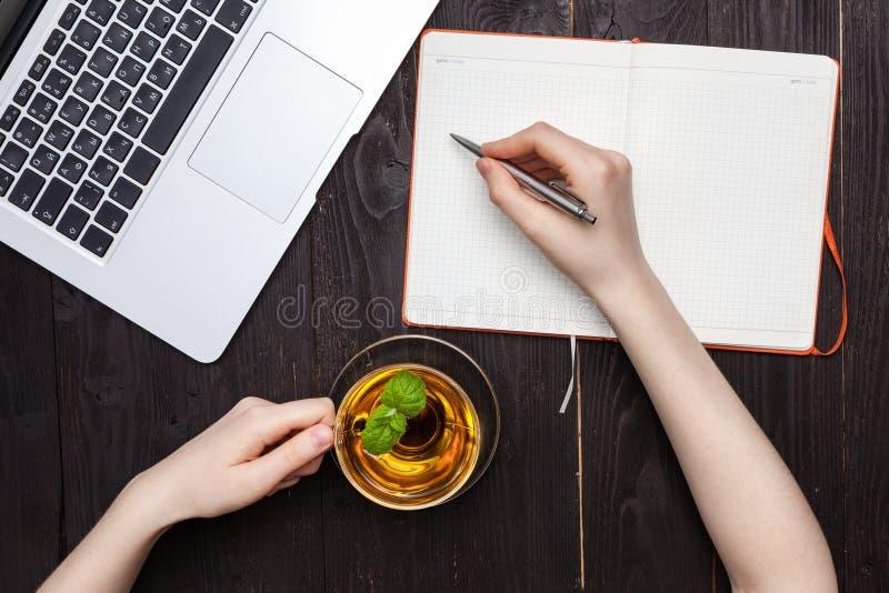 Руки женщины рисуя или писать с ручкой в открытой тетради стоковое фото rf