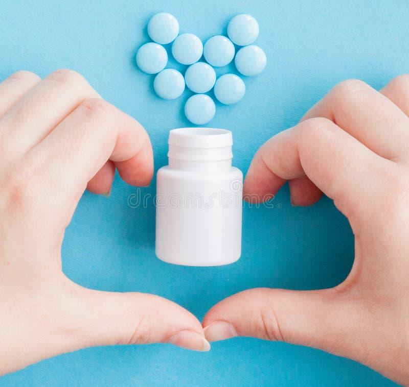 Руки женщины создали форму сердца пилюльки белые Глумитесь вверх для специальных предложений как реклама или другие идеи Медицинс стоковые фотографии rf