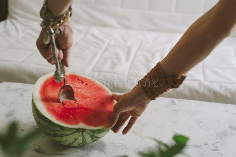 Руки женщины с ложкой в арбузе r стоковое изображение