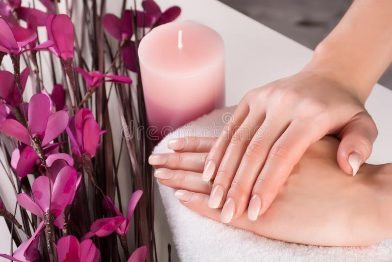 Руки женщины с ногтями Ombre французскими и фиолетовый цветок с ароматичной свечой в курорте стоковая фотография