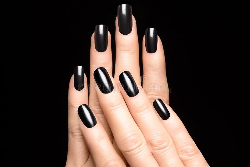 Руки женщины с черными ногтями стоковое изображение
