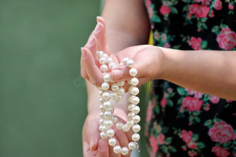 Руки женщин держа жемчуг отбортовывают украшения Крупный план женской руки с ювелирными изделиями жемчуга Женская рука держа стро стоковые фото