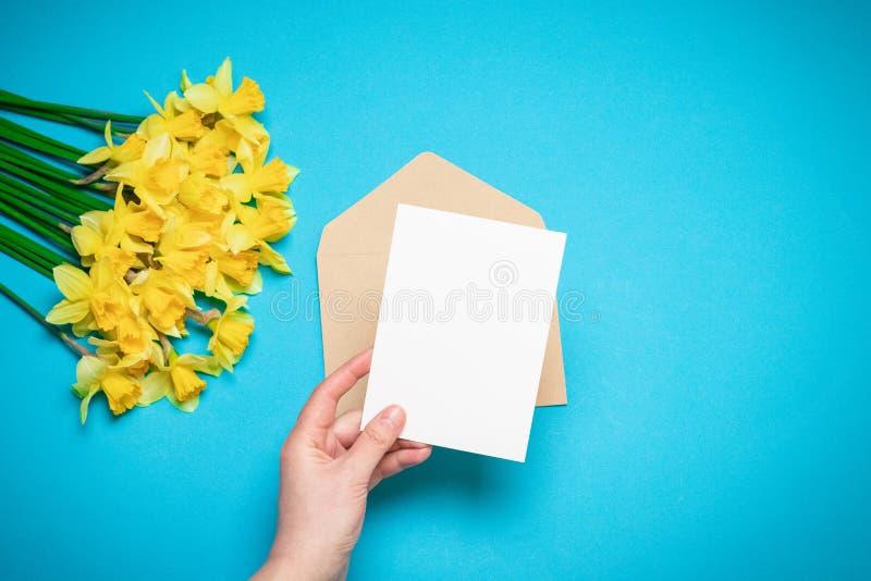 Руки женщин, конверт с письмом, цветки весны Плоское положение, взгляд сверху, космос экземпляра Шаблон для блога стоковая фотография