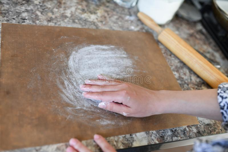Руки женщин подготавливая муку в процессе подготовки для печь Девушка подготавливая испечь стоковая фотография