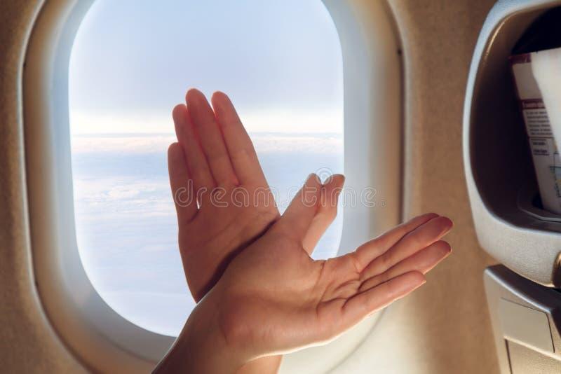 Руки женщин сложили в форму птицы пока в кабине перед фюзеляжем стоковые фотографии rf