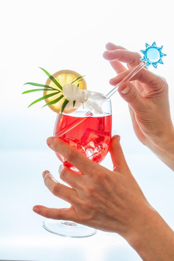 Руки женщин шевелят красочный тропический коктеиль с кубами льда, deco стоковое изображение rf