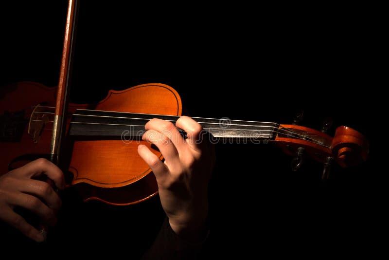 Руки играя скрипку изолированную на черноте стоковые фото