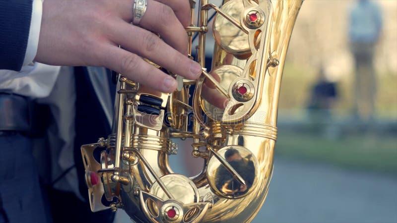 Руки игры groom на саксофоне Руки крупного плана человека играя золотой саксофон альта с световым эффектом Играть людей стоковые фото