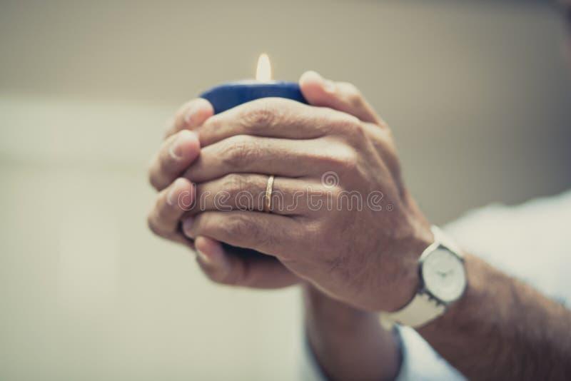 Руки и голубая свеча стоковые изображения